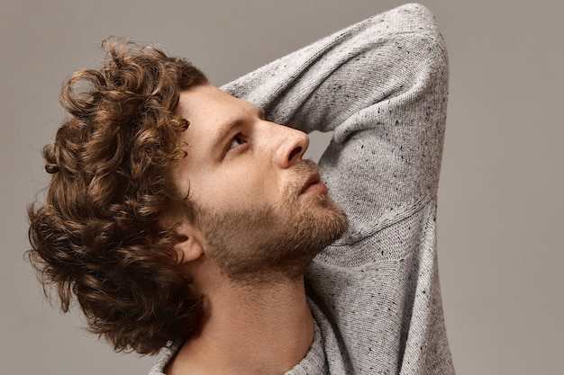 Stil, mode, männlichkeit und herrenbekleidung. porträt des stilvollen unrasierten mannes mit schönem profil, das sein lockiges haar berührt, mit nachdenklichem gesichtsausdruck aufblickend, grauen pullover tragend