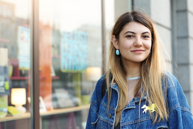 Stil und mode. städtische aufnahme der schönen charmanten jungen frau mit blondem haar gekleidet in der trendigen jeansjacke beim einkaufen im stadtzentrum, schauend und lächelnd, freizeit genießend