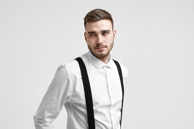 Stil und modekonzept. horizontale aufnahme des attraktiven jungen europäischen männlichen modells mit schnurrbart und stoppeln, die an der weißen studiowand aufwerfen, gekleidet in elegantem formellem hemd mit schwarzen hosenträgern