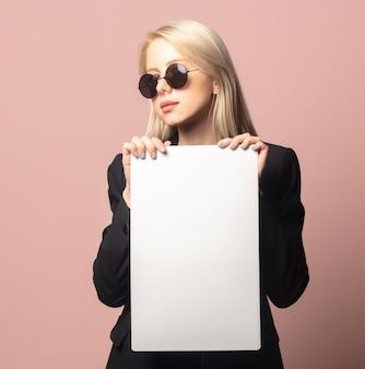 Stilblondine im blazer und in der sonnenbrille mit papier auf rosa hintergrund