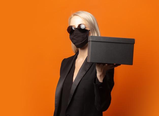 Stilblondine im schwarzen blazer mit geschenkbox auf einem üppigen orange hintergrund