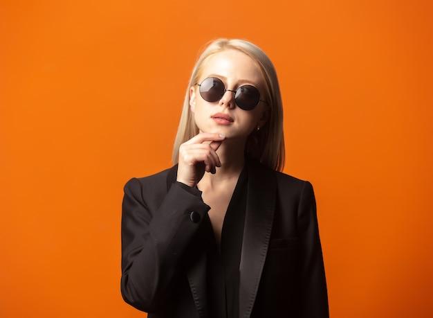 Stilblondine im schwarzen blazer und in der sonnenbrille auf einem üppigen orange hintergrund