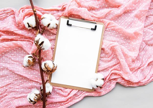 Stilisiert angeordnetes bürozubehörklemmbrett, baumwollblumen, schal. damenmode-accessoires. draufsicht der flachen lage