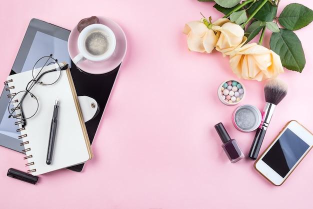 Stilisiertes feminines flatlay mit kaffeetasse, rosenblume, gläsern und tablette