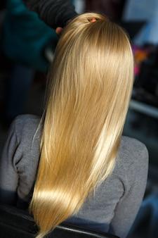 Stilist demonstrieren weibliches blondes haar