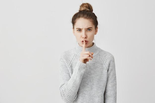 Stille! kopfschuss der kaukasischen frau, die zeigefinger auf den lippen hält. weibliche empfangsdame mit dunklem haar im brötchen gebunden, das bittet, still zu bleiben und shh über weißer wand zu sagen. schweigekonzept