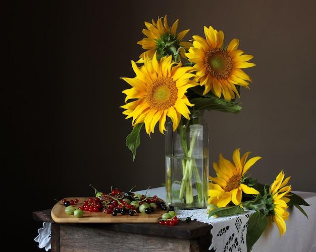 Stilleben mit einem bouquet von sonnenblumen und gartenbeeren