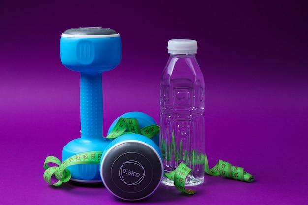 Stilles leben mit gesundem lebensstil. kurzhanteln, lineal, flasche wasser auf lila oberfläche.