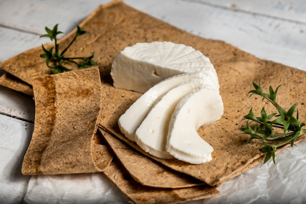 Stillleben adyghe-käse auf fladenbrot und basilikumblättern.