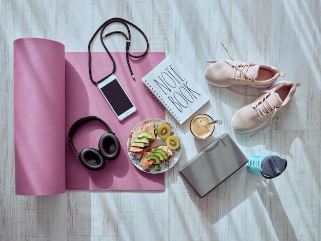 Stillleben auf dem bretterboden mit einem turnhallenvorhang, einem gesunden lebensmittel, musiksturzhelmen, einem kaffee, rosa schuhen, einer thermosflasche, einem anmerkungsbuch und einer halskette