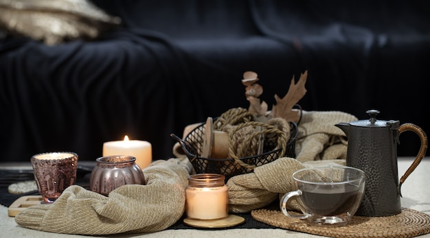 Stillleben auf dem tisch mit kerzen, pulloverbuch und herbstlaub. gemütliches wohnzimmer, inneneinrichtung.
