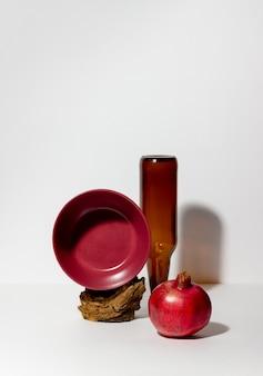 Stillleben aus einer braunen flasche, einem teller und einem granatapfel. entwurf. food-styling.