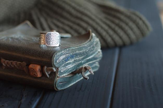Stillleben aus handgearbeitetem yerba mate-teeleder-kalebassenkürbis mit strohhalm, ledernotizbuch, pullover und ring auf schwarz lackiertem tisch,