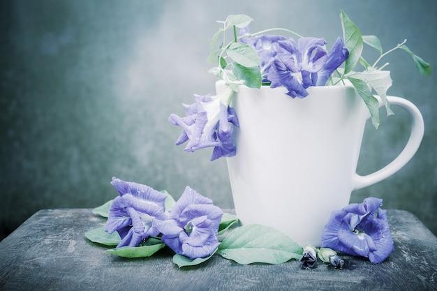 Stillleben blaue erbse oder schmetterlingserbse in der kaffeetasse auf holz.