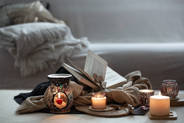 Stillleben brennender kerzen, bücher über pullover auf einem verschwommenen grauen hintergrund des raumes. wohnkomfort und wärme kopierraum.
