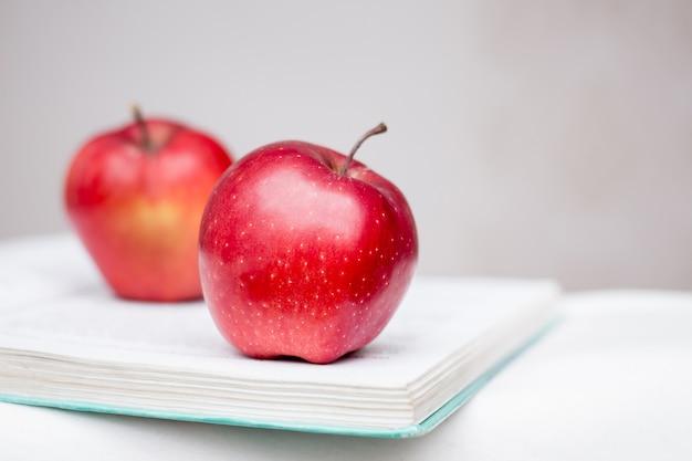 Stillleben der äpfel, die auf einem offenen buch liegen