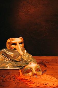 Stillleben der venetianischen karnevalsmaske mit federn gegen dunklen strukturierten hintergrund