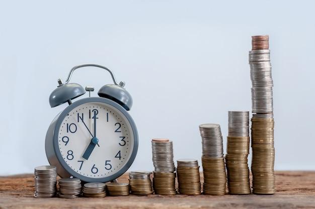 Stillleben des geldstapelschrittwachsens und des weckers