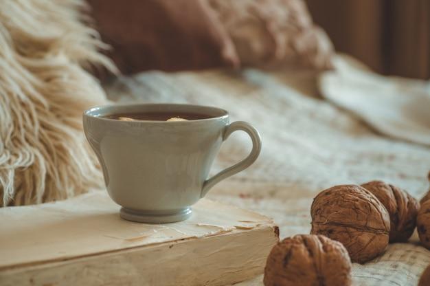 Stillleben details im innenraum des wohnzimmers. pullover und eine tasse tee mit kegel, nüssen und herbstdekor auf den büchern. lesen, ausruhen. gemütliches herbst- oder winterkonzept.