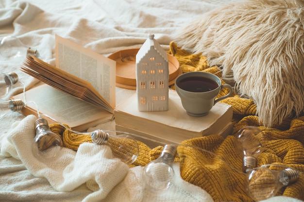 Stillleben details im innenraum des wohnzimmers. pullover und eine tasse tee mit kerzenhaus und herbstdekor auf den büchern. lesen, ausruhen. gemütliches herbst- oder winterkonzept.
