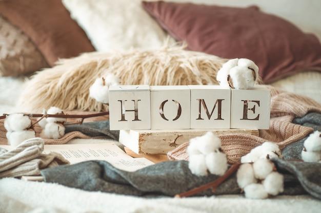 Stillleben details im innenraum des wohnzimmers und der inschrift home. bücher und eine tasse tee mit zapfen und baumwolle. lesen, ausruhen. gemütliches herbst- oder winterkonzept, strickwaren. gemütliches herbst-winter-konzept