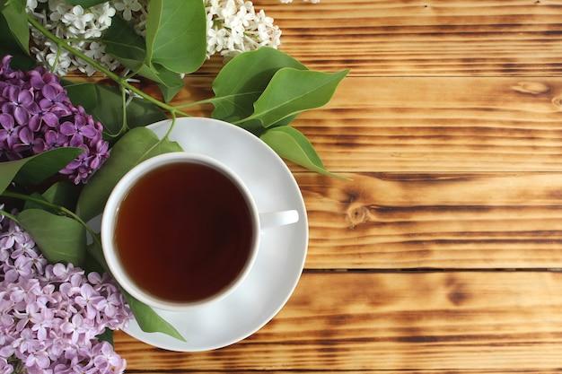 Stillleben, ein strauß frischer, schöner flieder mit einer tasse tee am frühen morgen. ein schöner blumenstrauß liegt auf dem tisch. platz für ihren text.