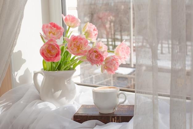 Stillleben eine vase mit tulpen und einem alten buch am fenster