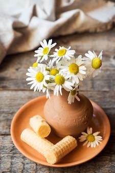Stillleben eines straußes von gänseblümchen in einer vase und in waffelrohren. rustikaler holzstil.