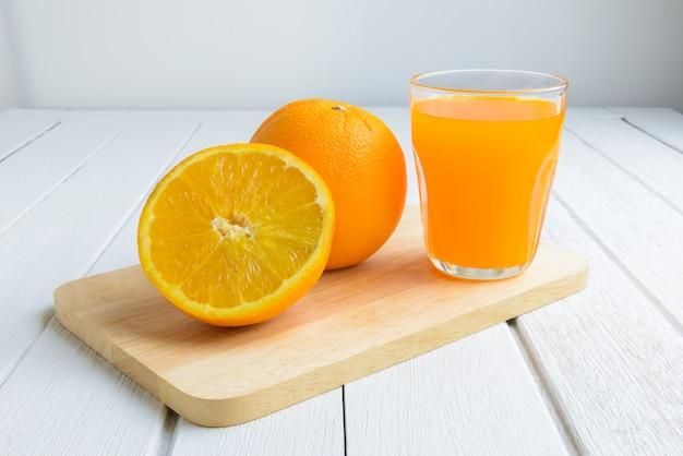 Stillleben-frische orange frucht, orangensaft auf weinlese-weißer hölzerner tabelle