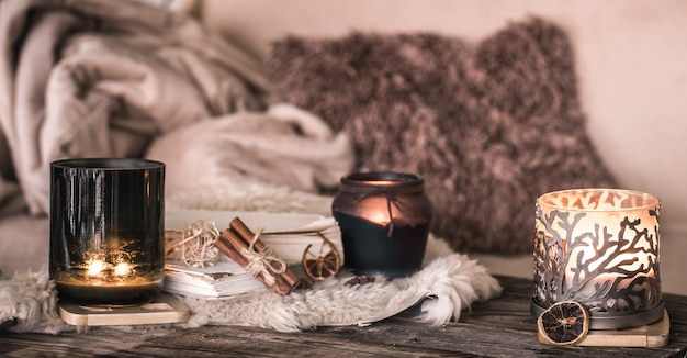 Stillleben häusliche atmosphäre im innenraum mit kerzen und einem buch an der wand von gemütlichen tagesdecken