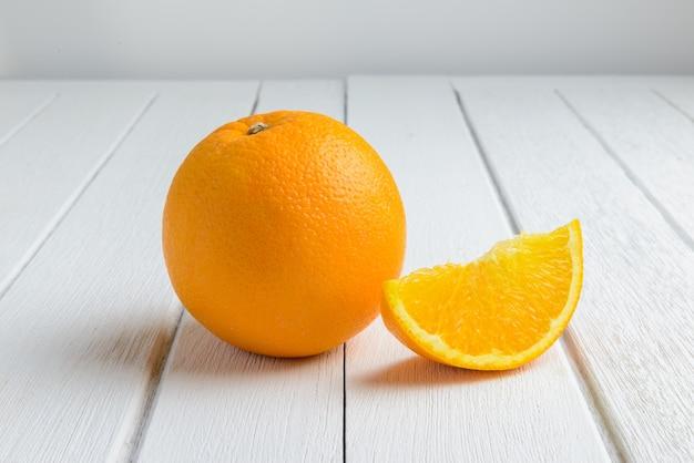 Stillleben-halber halbmond, volle frische orange frucht auf weinlese-weißer hölzerner tabelle