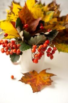Stillleben. herbstblumenstrauß aus hellen gefallenen blättern und roter vogelbeere in einer weißen tasse auf einem hölzernen hintergrund. vertikales foto
