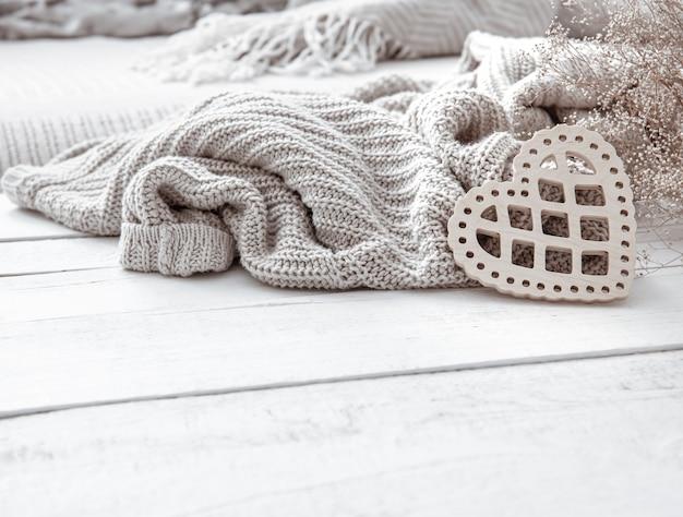 Stillleben im hygge-stil mit dekorativem herzen und gestricktem element auf holzoberfläche