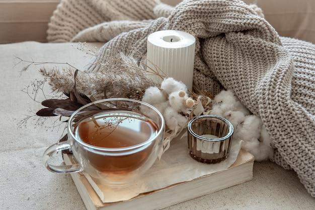 Stillleben im skandinavischen stil mit einer tasse tee, einem gestrickten element und einem buchkopierraum.