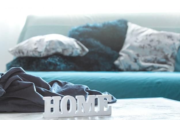 Stillleben in blautönen, mit holzinschrift zu hause und dekorativen elementen im wohnzimmer.