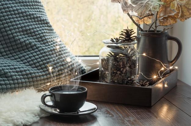 Stillleben in wohngebäude. gemütlicher herbst oder winter. gemütliches winter- oder herbsttasse kaffee zu hause warmes flaumiges pelzfell, girlande, schwedisches hygge konzept.