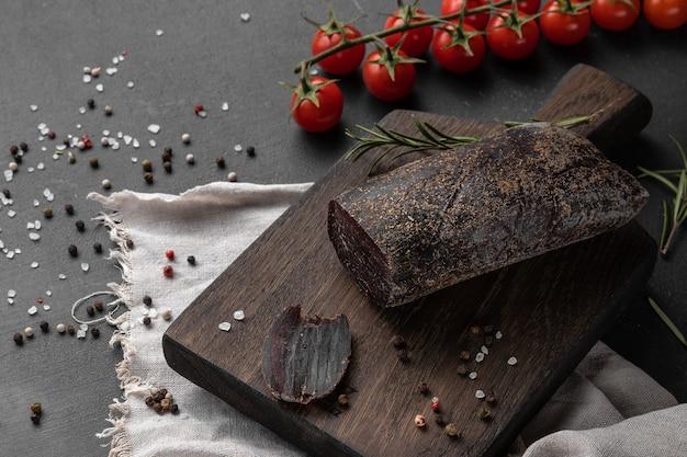Stillleben-komposition mit einem stück rot geräuchertem trockenem schinken von elchfleisch auf einem hölzernen schneidebrett, seitenansicht