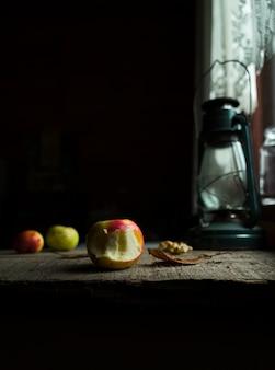 Stillleben mit äpfeln, gefallenem blatt und laterne auf altem holztisch durch fenster