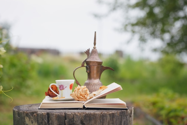 Stillleben mit antikem krug, offenem buch, getrockneter rose und tasse kaffee