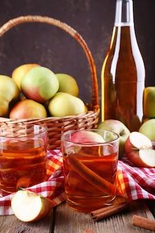 Stillleben mit apfelwein und frischen äpfeln auf holztisch
