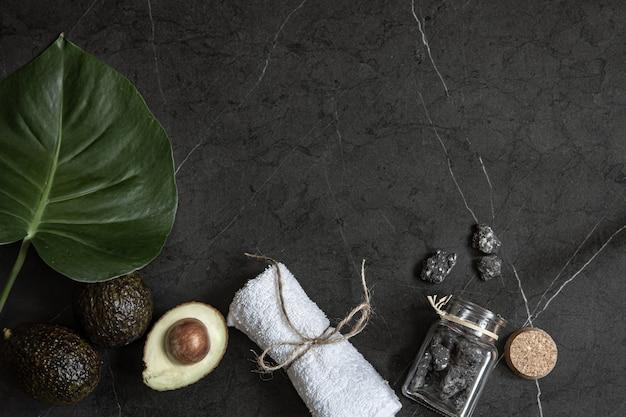 Stillleben mit avocado, handtuch und steinen auf einer dunklen marmoroberfläche. gesichts- und körperhautpflegekonzept.
