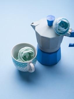 Stillleben mit blauer kaffeemaschine und blume