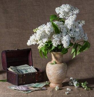 Stillleben mit blühenden fliederzweigen in der vase und dollar in der brust