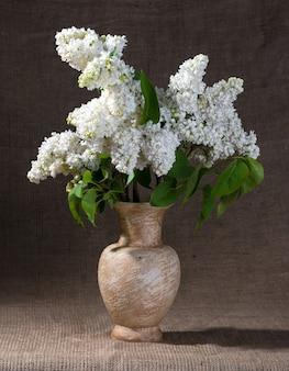 Stillleben mit blühenden fliederzweigen in der vase
