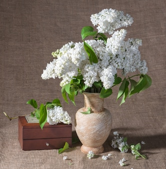 Stillleben mit blühenden fliederzweigen in vase und truhe