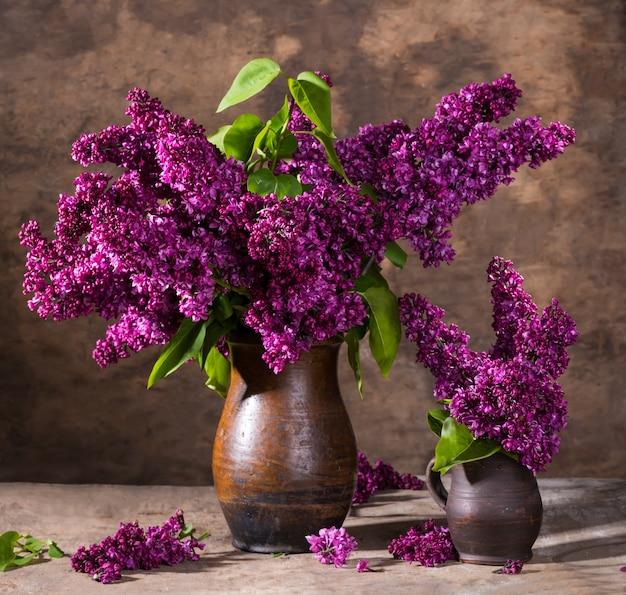 Stillleben mit blühenden fliederzweigen in vasen