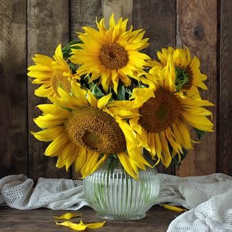 Stillleben mit blumenstrauß von sonnenblumen in einem glaskrug.