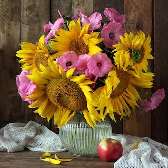 Stillleben mit bouquet von sonnenblumen in einem glaskrug und apfel.