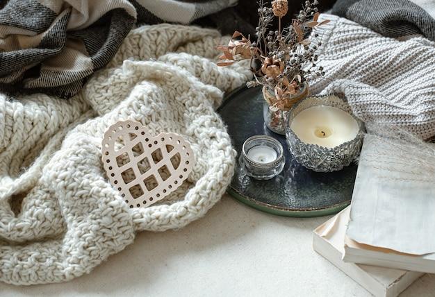 Stillleben mit dekorativem herzen, bücher und kerzen in kerzenhaltern. das konzept des valentinstags und der wohnkultur.