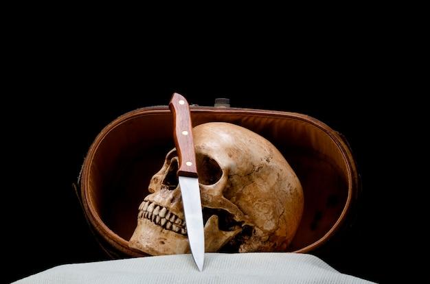 Stillleben mit dem menschlichen schädel und messer werden in den alten ledernen kasten gelegt, der auf schwarzem hintergrund lokalisiert wird